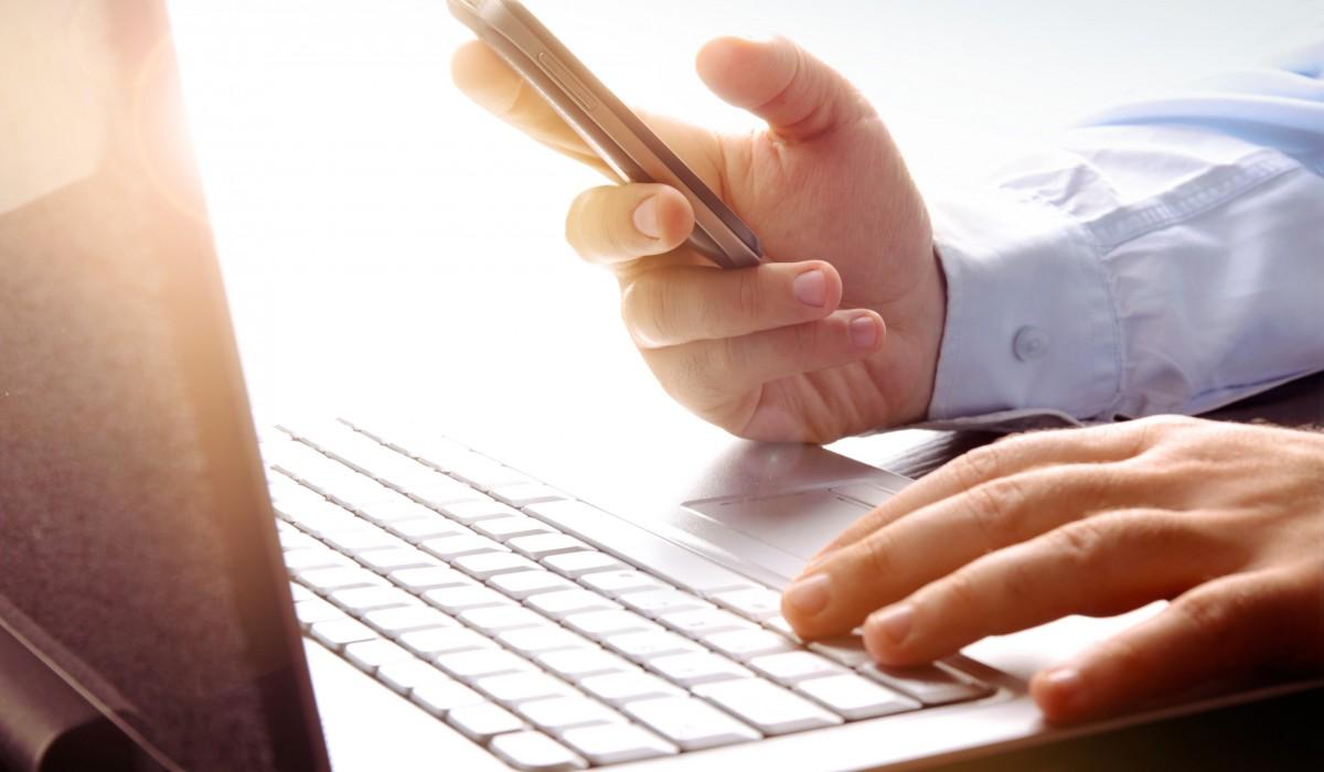 laptop + phone in hand -1200x700.jpg